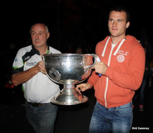 Neil McGee & his father Éamonn carry the Sam Maguire into the Gaoth Dobhair clubhouse last night. Pic Brid Sweeney