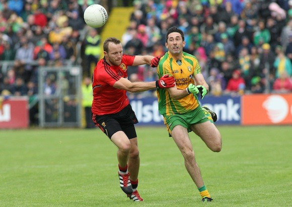 Rory Kavanagh gets his pass forward despite Ambrose Rodgers' tackle