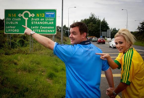 Danny O'Carroll and his wife Amanda Woods who will be supporting two different sides in this weekend semi-final between Dublin and Donegal.The couple are pictured at the roundabout near to their home in Co Donegal with Danny supporting the blues and his wife Amanda supporting Donegal as she points out Michael Murphy's signature  on the Dublin shirt. Photo Brian McDaid/Cristeph Studio