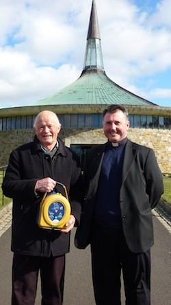 Henry presents the defibrillator to Fr Sweeney at St. Aengus', Burt.