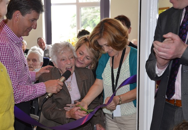 Madge O'Donnell cutting the ribbon assisted by Sue Islam, Director of Nursing at Dungloe Hospital on the right and Daniel O'Donnell on the left.
