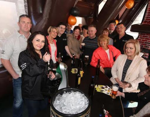 Family and friends help Catriona pull the first pint at the Pop-Up-Pub!