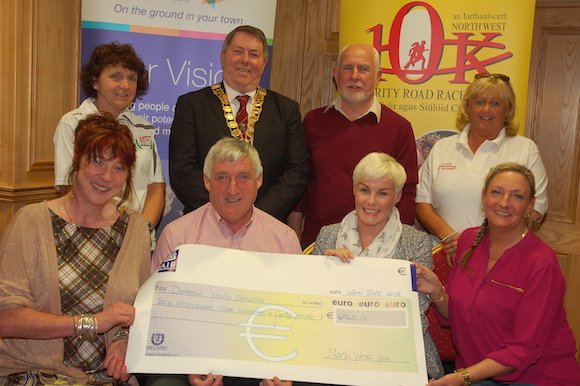 North West 10k Chairperson James Boyle presenting a cheque for 6,940 euro to Donegal Youth Service committee members Marina Carlin (Chairperson), Lorraine Thompson (Regional Director) and Charlene Logue (Chairperson). At back are North West 10k Committee members Nancy McNamee and Bernie Brennan with the Mayor of the Letterkenny Municipal District Cllr Gerry McMonagle and Frank Dooley (DYS Director)