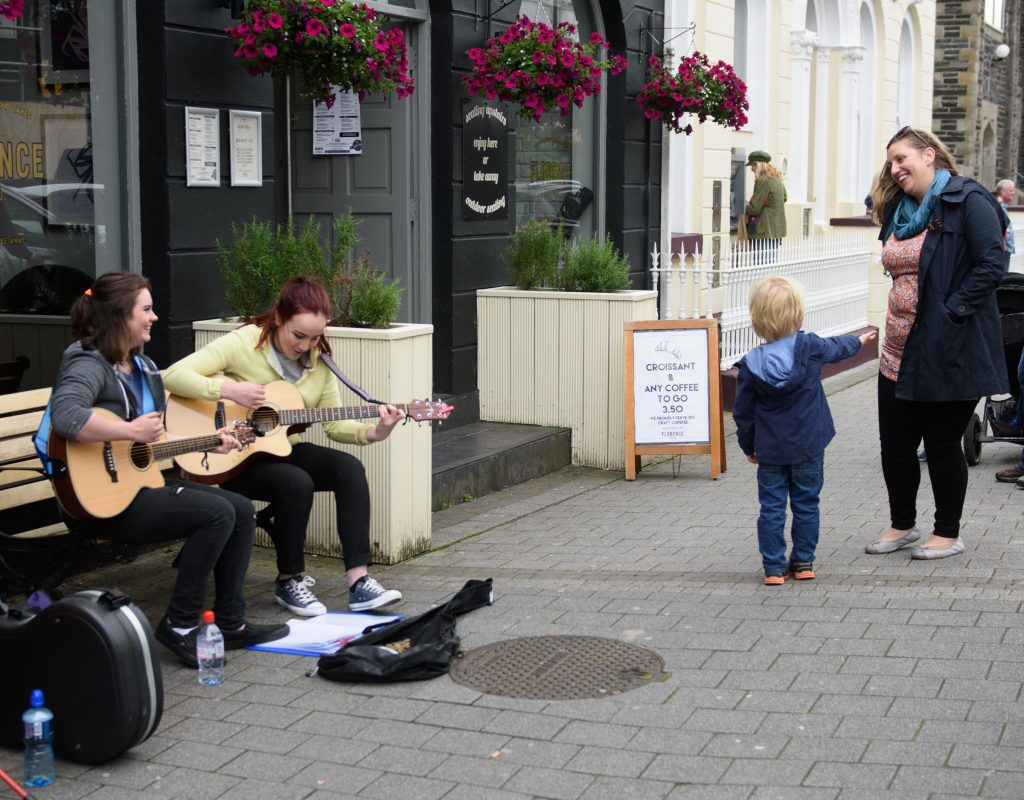 A young lad looking ofr money for buskers Niamh O'Raw  and Emer McLaughlin from Buncrana taking part in the Letterkenny Chamber Shop LK busking Competition in Letterkenny on Saturday last.  Photo Clive Wasson