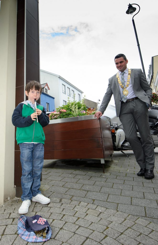John Pat McDaid, letterkenny Mayor watching Conor McCarthy from Carrigart taking part in the Letterkenny Chamber Shop LK busking Competition in Letterkenny on Saturday last.  Photo Clive Wasson