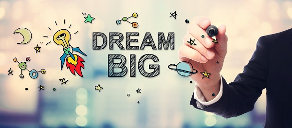 Businessman drawing Dream Big concept on blurred abstract background