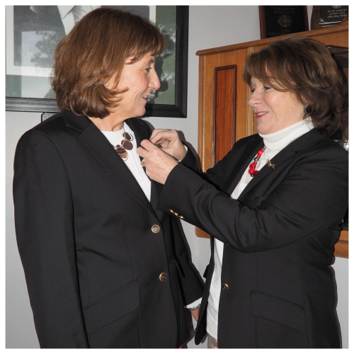 Lady Captain, Roseanne Logue receiving her Captains pin from Mary Flynn, outgoing Captain.